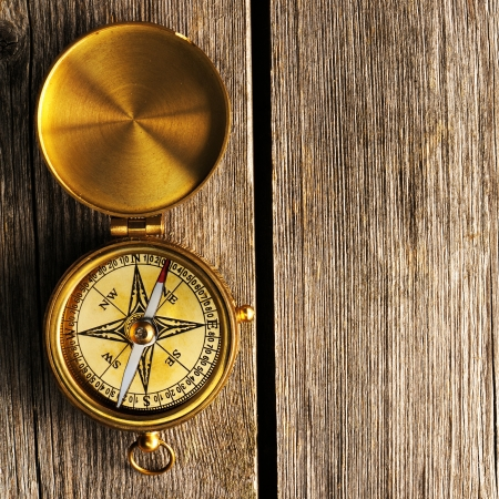 explore: Antique brass compass over wooden background