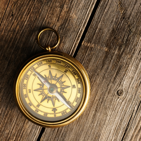 Antique brass compass over wooden background Stock Photo - 19358814