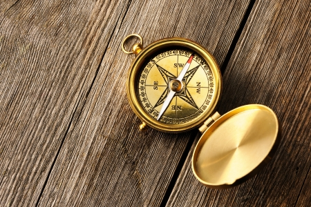Antique brass compass over wooden background Stock Photo - 19358853