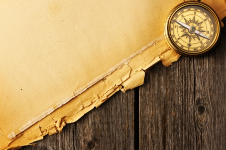 traverse: Antique brass compass over old paper background