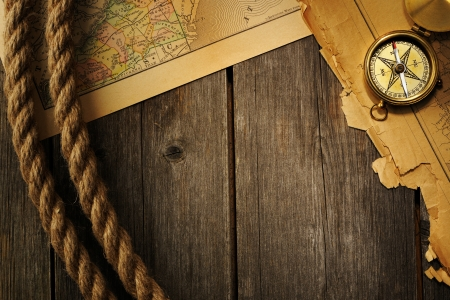 traverse: Antique brass compass and rope over old map Stock Photo