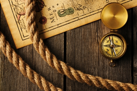 Antique brass compass and rope over old map Stock Photo
