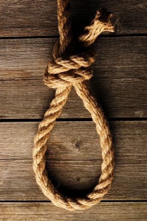 gallows: Rope noose with knot over old wooden background