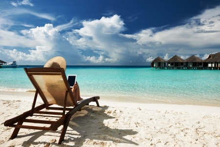 Young woman in hat with tablet pc at the beach