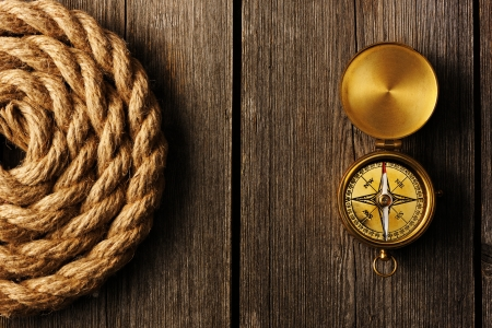 traverse: Antique brass compass and rope over wooden background
