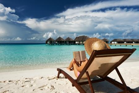 mujer leyendo libro: Mujer joven que lee un libro en la playa