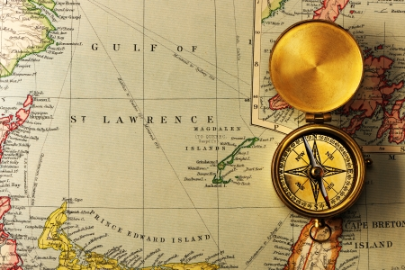 Antique brass compass over old XIX century map photo