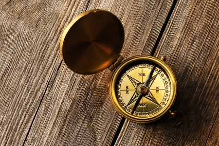 Antique brass compass over wooden background photo