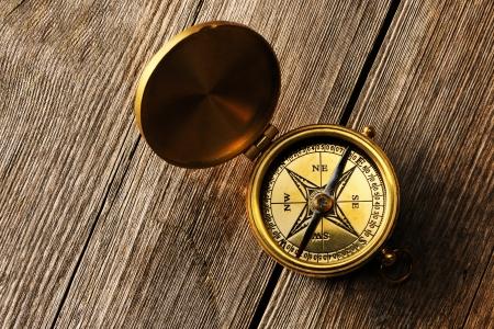 brujula antigua: Comp?de cobre amarillo sobre fondo de madera