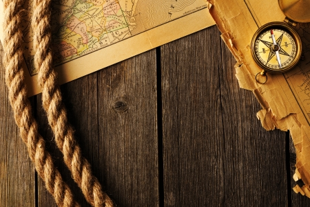 old fashioned: Antique brass compass and rope over old map Stock Photo