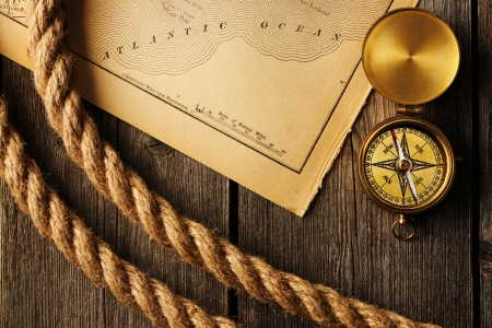 Antique brass compass and rope over old map photo