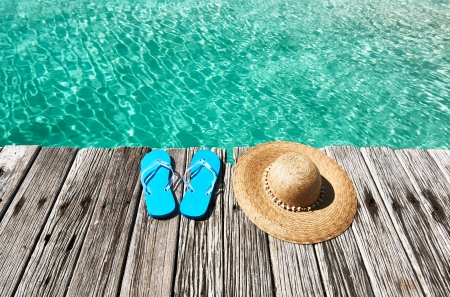 Slippers and hat at jetty by the sea photo