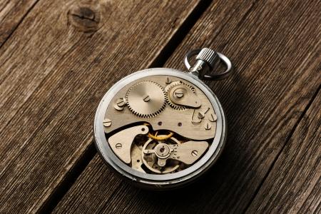 clock gears: Clockwork mechanism over wooden background  Stock Photo