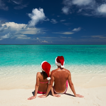Couple in santa's hat on a tropical beach at Maldives photo