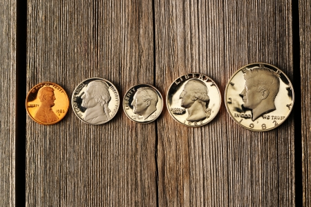 Five US cent coins over wooden background photo