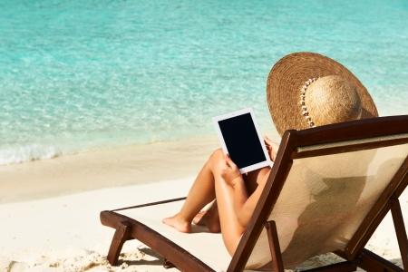 Mujer joven en sombrero con el Tablet PC en la playa Foto de archivo - 20573168
