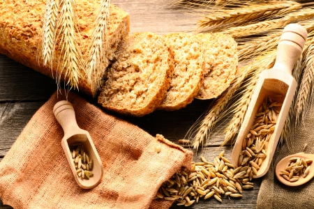 Rye spikelets and sliced bread on wooden background photo