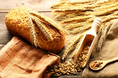 Rye spikelets and bread on wooden background photo