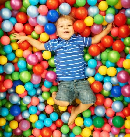 Glückliches Kind spielt mit bunten Kunststoff-Kugeln Spielplatz hohe Sicht