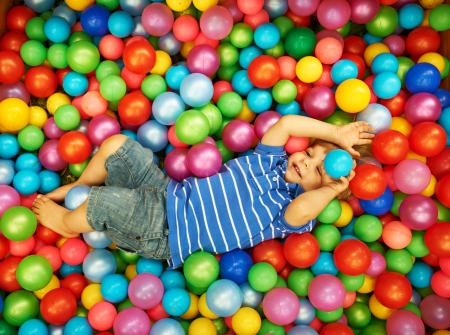 group of colourful ball: Happy child playing at colorful plastic balls playground high view Stock Photo