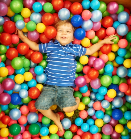 bola de billar: Niño feliz jugando en las bolas de plástico de colores, vista, parque infantil