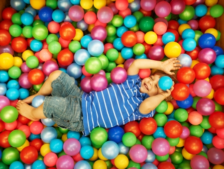 pool balls: Happy child playing at colorful plastic balls playground high view Stock Photo