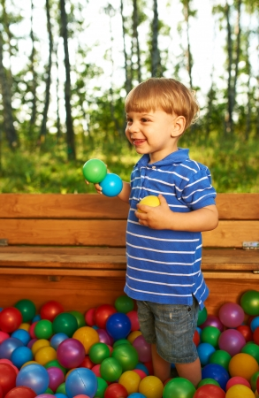 playcentre: Happy child playing at colorful plastic balls playground high view Stock Photo