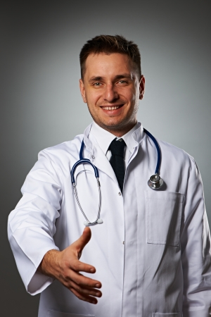 Medical doctor with stethoscope giving hand for handshaking against grey background  photo