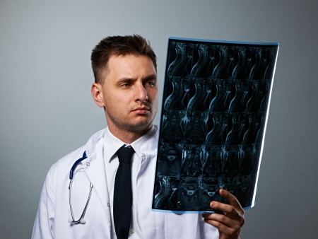 Medical doctor with MRI spinal scan portrait against grey background  photo