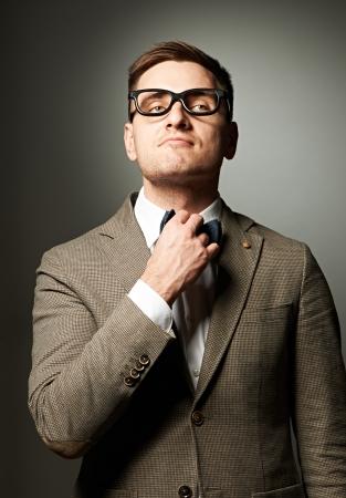 adjust: Confident nerd in eyeglasses adjusting his bow-tie against grey background