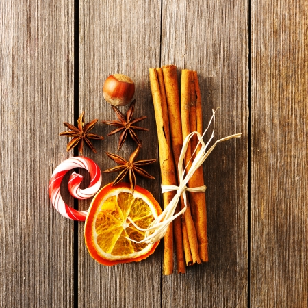 Cinnamon sticks and other spices over wooden table photo