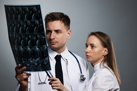 imaging: Medical doctors team with MRI spinal scan portrait against grey background  Stock Photo