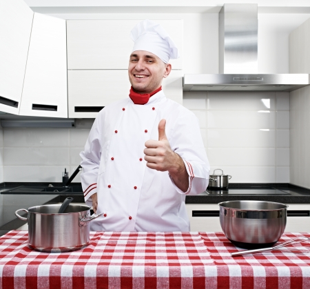 Male chef at kitchen with thumb up photo