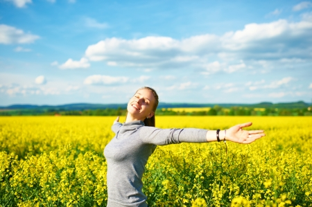 Girl with outstretched arms at colza field Stock Photo - 23455379