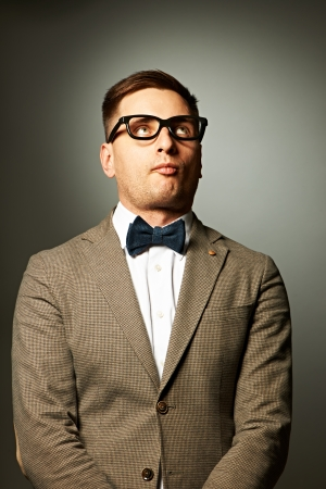 geek: Confident nerd in eyeglasses and bow tie against grey background