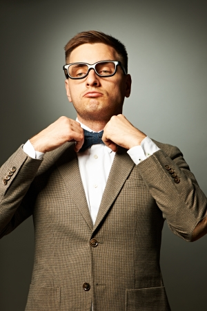 silly face: Confident nerd in eyeglasses adjusting his bow-tie against grey background