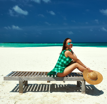 Woman in green dress on a tropical beach at Maldives photo