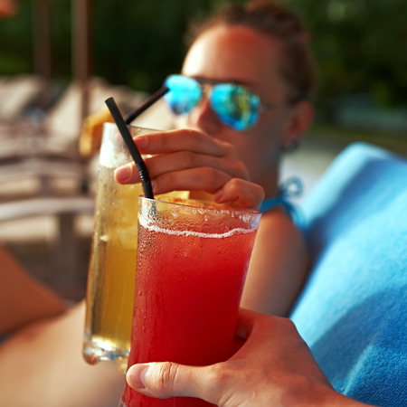 luxury party: Couple clinking glasses with cocktails at poolside
