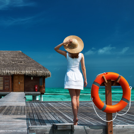 Woman on a tropical beach jetty at Maldives photo