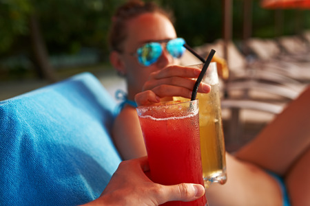 Couple clinking glasses with cocktails at poolside photo
