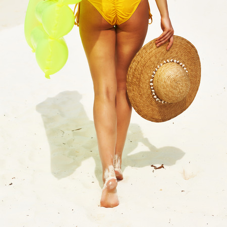 Woman with yellow inflatable raft walking at the beach photo