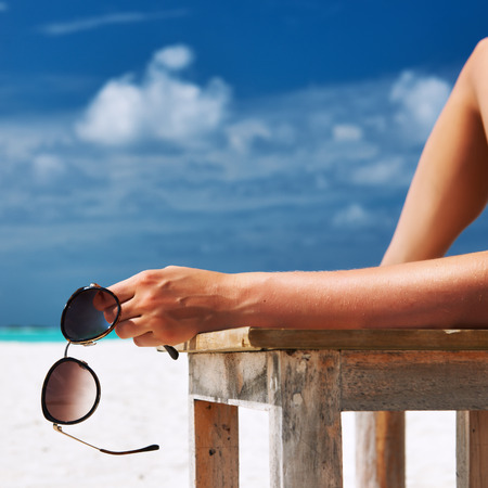 Woman at beautiful beach holding sunglasses photo