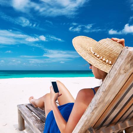 playas tropicales: Mujer joven en el sombrero con el tel�fono m�vil en la playa