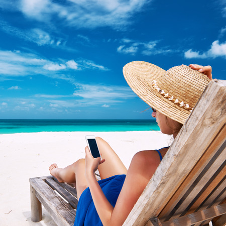 tropical beaches: Young woman in hat with mobile phone at the beach Stock Photo