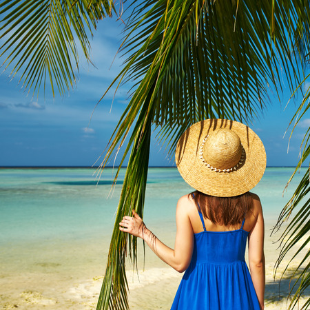 Woman in blue dress on a tropical beach at Maldives photo