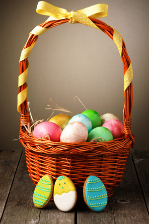 Colored easter eggs in basket on wooden table photo