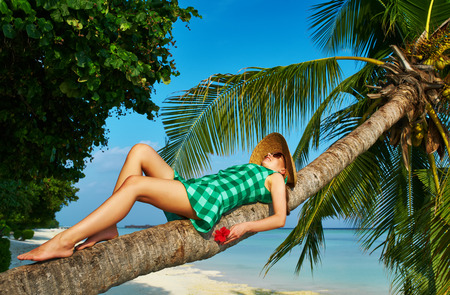 Woman in green dress lying down on a palm tree at tropical beach, Maldives photo