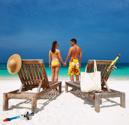 Couple in yellow on a tropical beach at Maldives photo