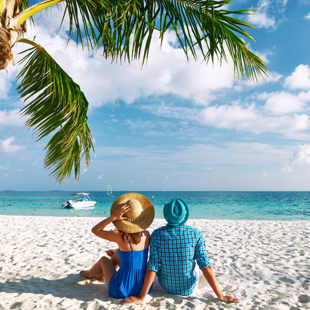 woman beach dress: Couple in blue clothes on a tropical beach at Maldives