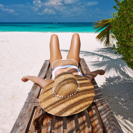 chaise lounge: Woman at beautiful beach lying on chaise lounge